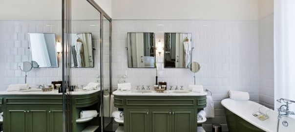 modern coloured bathroom suite with ornate tile floor and avocado green wood sink cabinets