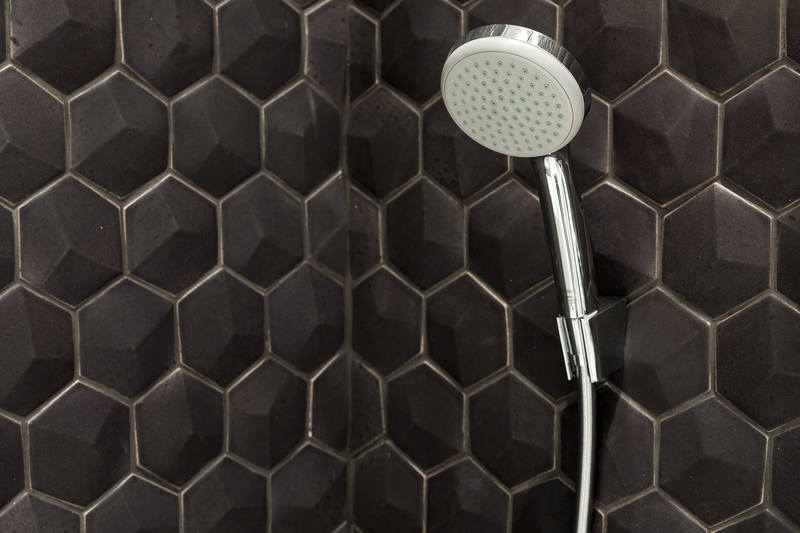Black shower tiles and shower head